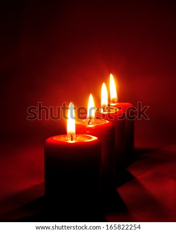 Red candles flaming on red background