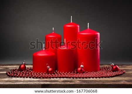 red candles on wooden table on gray background. Christmas  - stock photo