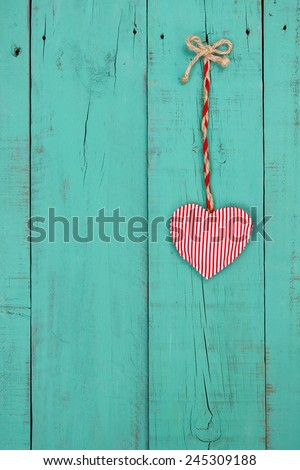 Red candy cane striped fabric heart hanging by rope on antique teal blue rustic wooden background - stock photo