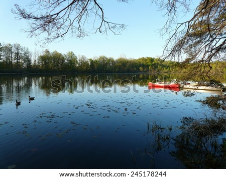 Red canoe and peaceful lake in the morning calm, near Stratford, Ontario, Canada - stock photo