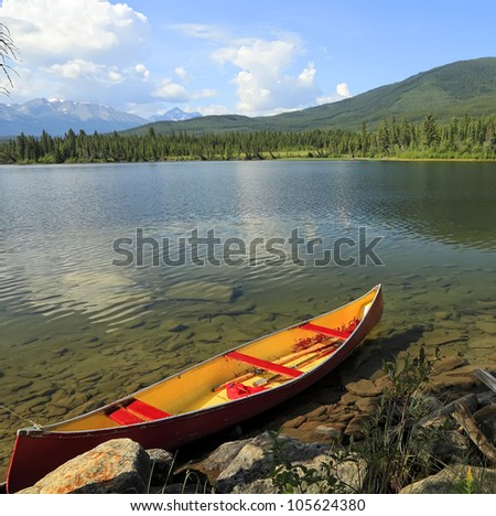 Red canoe moored on the bank of the mountain lake - stock photo
