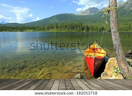 Red canoe mooring at the wooden floor background. Jasper National Park, Alberta, Canada    - stock photo