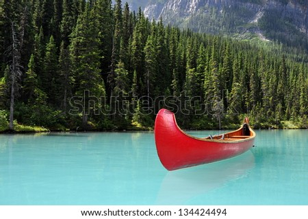 Red Canoe on Glacial lake - stock photo