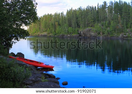 Red canoe sitting on the rocks at the lake in Minnesota, USA - stock photo