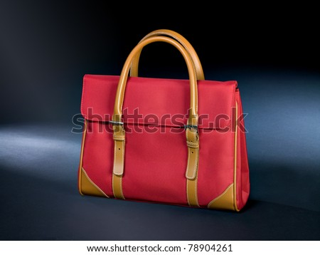 Red canvas handbag with some parts made of leather