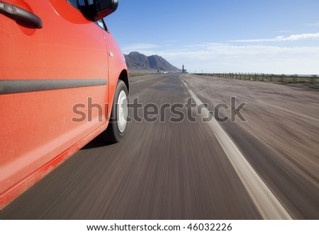 Red car driving through the country at high speed