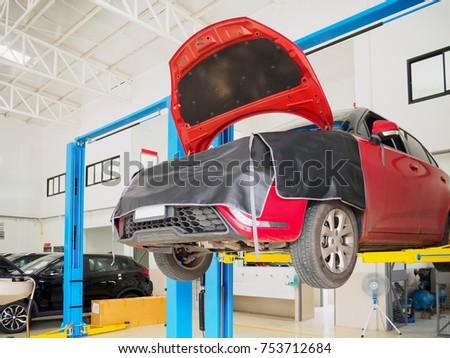 Red car in auto service centre station for repair and maintenance