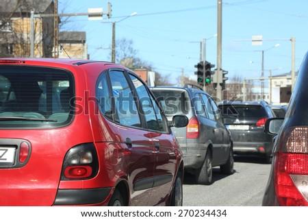 Red car in traffic. Urban street. - stock photo