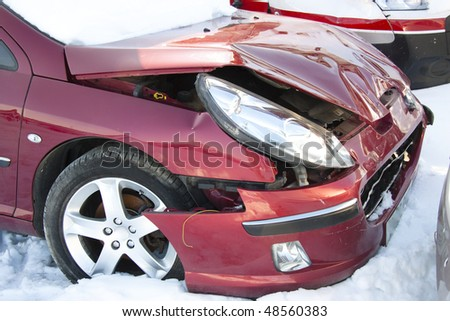 Red car in winter crushed. Damage front of vehicle. - stock photo