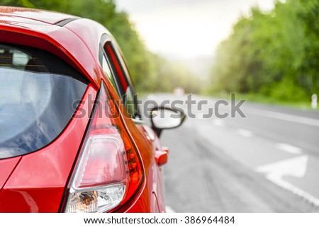 Red car on the road at sunset.  - stock photo
