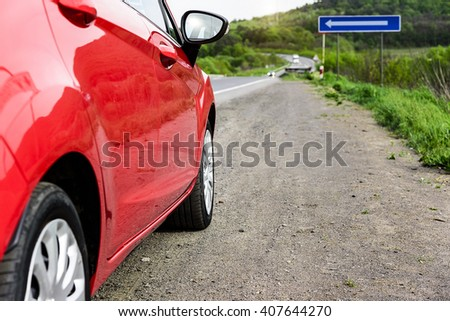 Red car parked on the roadside. Travel concept. - stock photo