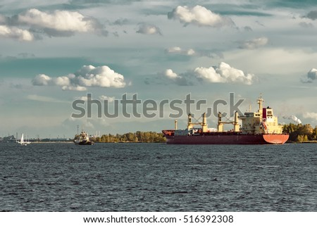 Red cargo ship and the tug ship guide it to the port
