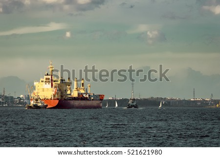 Red cargo ship and the tug ship towing  it to the port