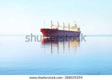 Red cargo ship (bulk carrier with cranes on deck) sailing in still water with a reflection - stock photo