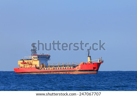 Red cargo ship in a distance in the sea