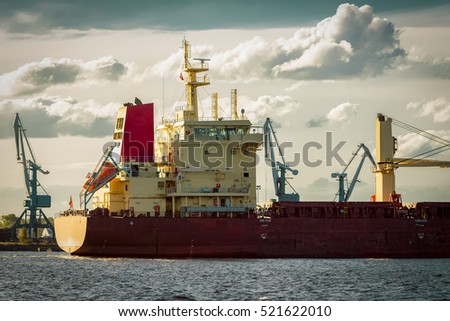 Red cargo ship's stern against port cranes