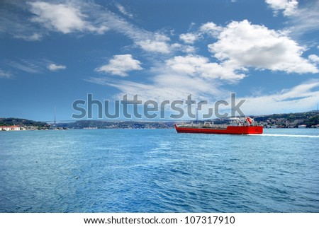 Red cargo ship sailing in to the sea - stock photo