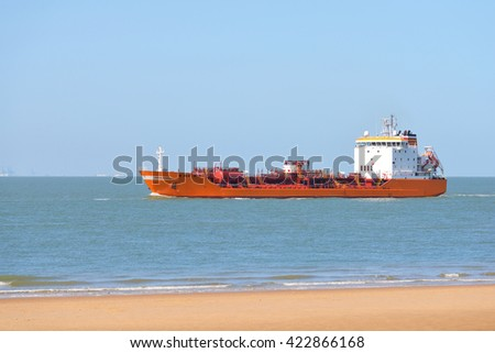 Red cargo tanker ship sailing next to the coast of Vlissingen, the Netherlands - stock photo