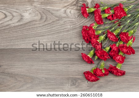 red carnations on wooden table - stock photo