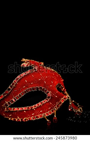 Red carnival mask with golden ornaments and pearls over black background - stock photo