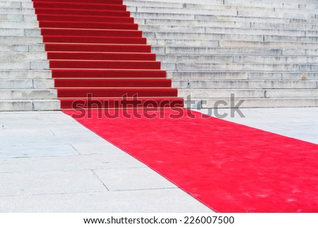 Red carpet on staircase marking the route taken by celebrities on ceremonial events - stock photo