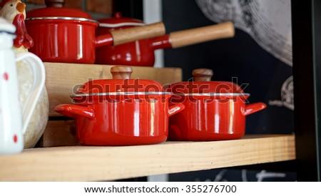 Red Casserole Pots on Wooden Shelf - stock photo