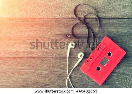 Red cassette tape with earphone over wooden table. top view. Retro or vintage color filtered. Old time concept. Nostalgia concept.