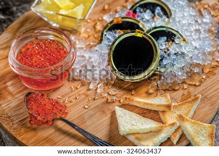 Red caviar and caviar. Spoon of red caviar and open cans of caviar. On the ice are banks with black caviar with slices of bread