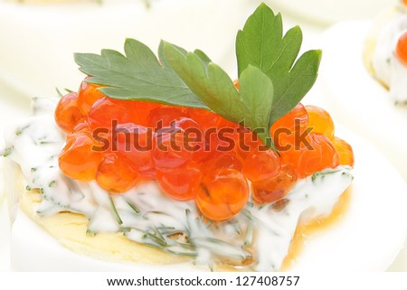 Red caviar on a boiled egg with parsley leaves