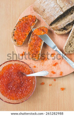 Red caviar toasts sandwich with silver knife, bowl of tasty red caviar with spoon and fresh baked homemade healthy bread on a wooden table background - stock photo