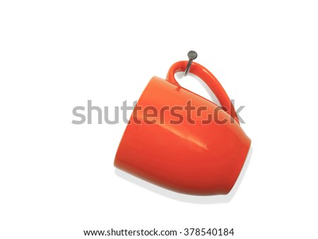 Red Ceramic Coffee Cup Hanging on Bent Nail on a White Background - stock photo
