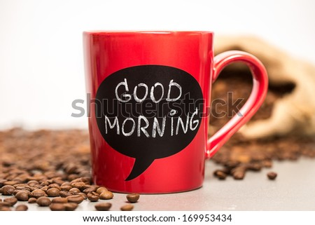 Red ceramic cup with good morning sign made with chalk. Standing on a kitchen table with coffee beans. - stock photo