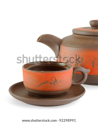 red ceramic cup with tea and kettle, over white background