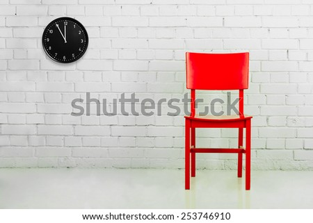 Red chair against white brick wall with clock - stock photo