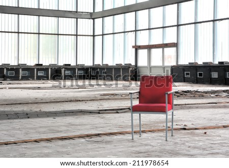 Red chair in an abandoned dilapidated event room - stock photo