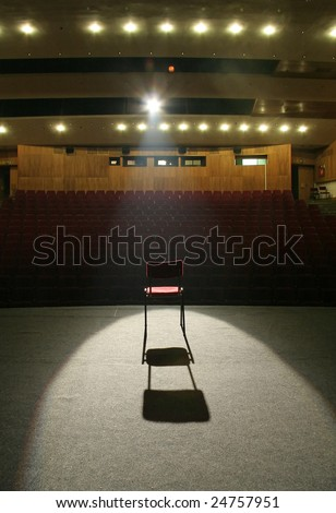 red chair on brown stage lighted with a spotlight, empty seats in background