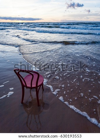 red chair on the beach in the morning. Long exposure shot. Latvia
