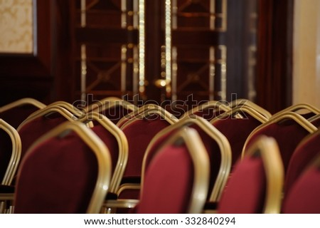 red chairs in an empty, dimly lit conference hall - stock photo