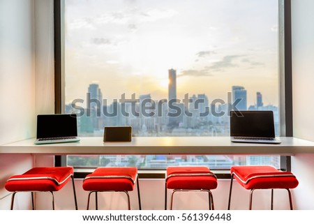 red chairs in modern design arranged by a long wall mounted table with laptops and tablets