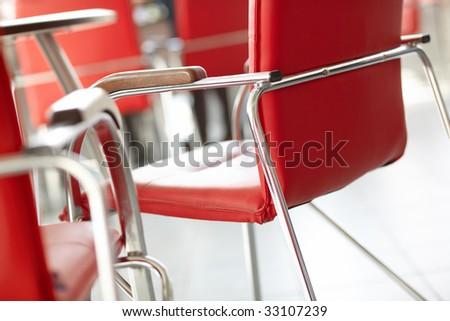 Red chairs in the office or at the waiting room. Focus on the further object. - stock photo