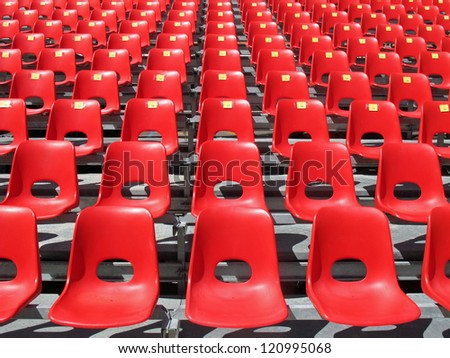 Red chairs of empty stadium but ready to accommodate the fans during the match - stock photo