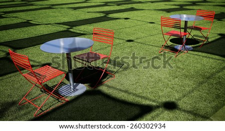 Red chairs on green field with pattern of shadows - stock photo