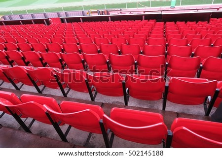Red chairs row in football stadium.