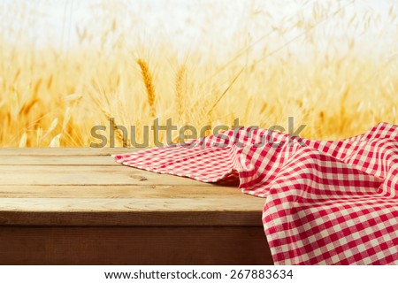 Red checked tablecloth on wooden deck table over wheat field background - stock photo