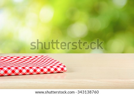 Red checkered cloth on wood table top in green bokeh abstract background - can be used for display or montage your products - stock photo