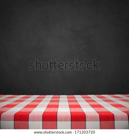 Red checkered tablecloth on black chalkboard - stock photo