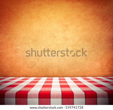 Red checkered tablecloth on textured wall - stock photo
