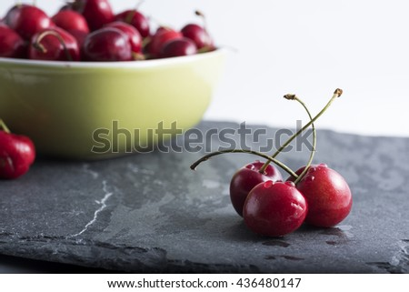 red cherries cutlery on dark stone and in the background a bowl with cherries .