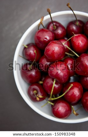 Red cherries in a white bowl - stock photo