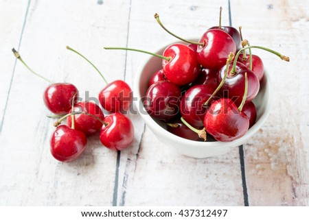 red cherries in a white ceramic bowl